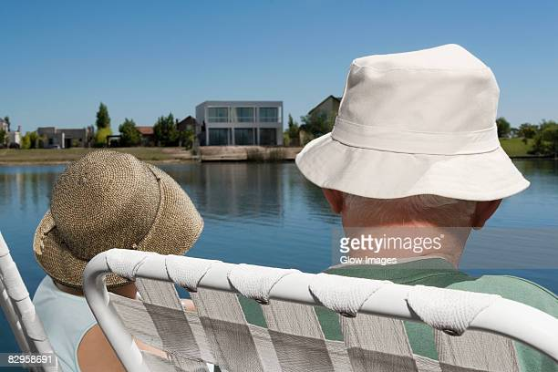 Rear view of a couple sitting on chairs at the lakeside