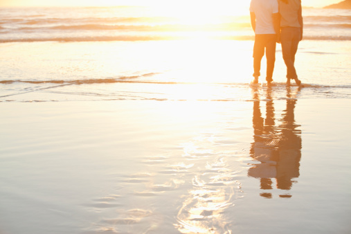Rear view of a couple standing together on beach at sunset - gettyimageskorea