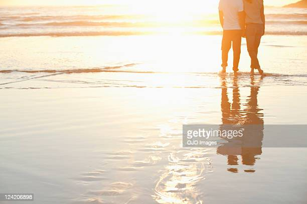Rear view of a couple standing together on beach at sunset
