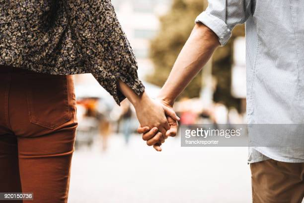 rear view of a couple walking on the street - holding hands stock pictures, royalty-free photos & images