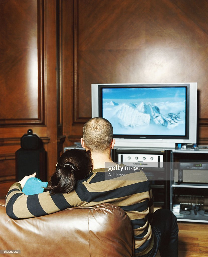 Rear View of a Couple Watching a Widescreen Television : Stock Photo