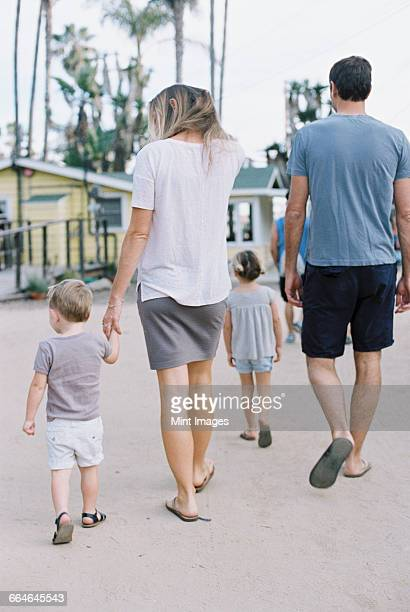 Rear view of a family, a couple walking with their young son and daughter.