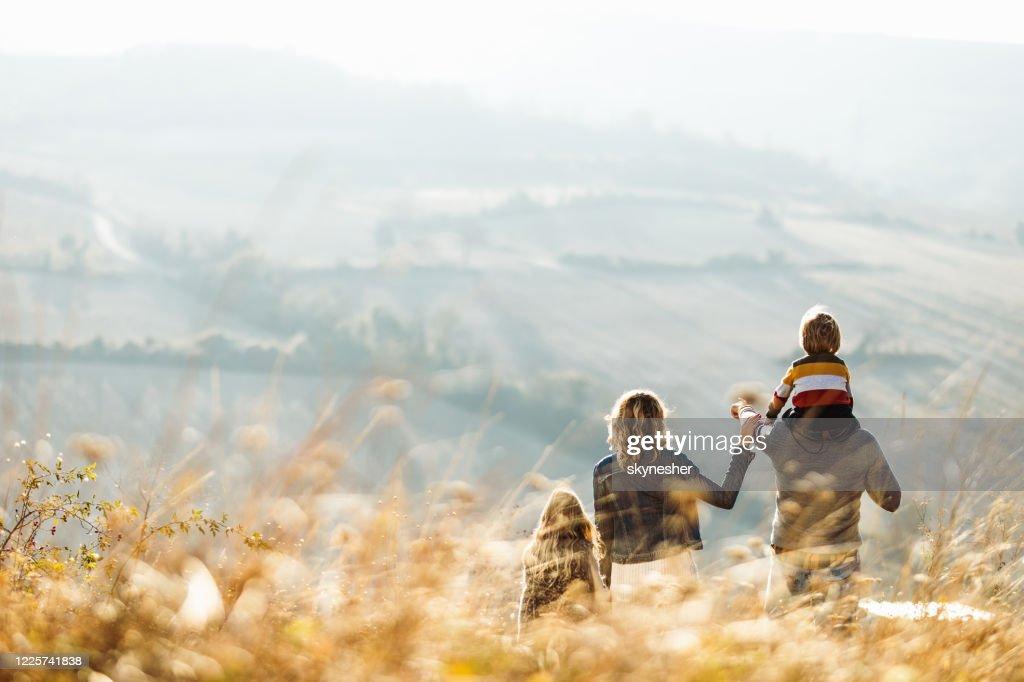 Vista trasera de una familia de pie en una colina en el día de otoño. : Foto de stock