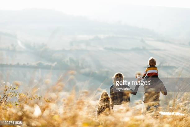 achtermening van een familie die zich op een heuvel in de herfstdag bevindt. - buitenopname stockfoto's en -beelden