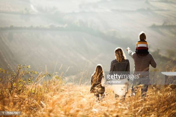 rear view of a family walking down the hill in autumn day. - aiming stock pictures, royalty-free photos & images