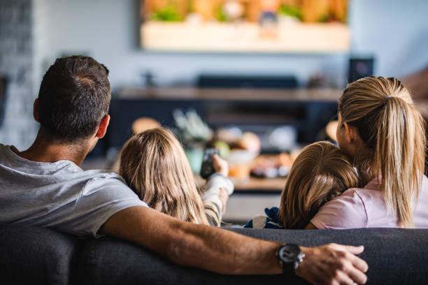 vista traseira de uma família assistindo tv no sofá em casa. - tv - fotografias e filmes do acervo