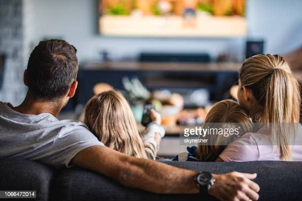 rear view of a family watching tv on sofa at home. - togetherness stock pictures, royalty-free photos & images
