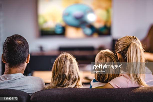 rear view of a family watching tv on sofa at home. - family watching tv stock pictures, royalty-free photos & images