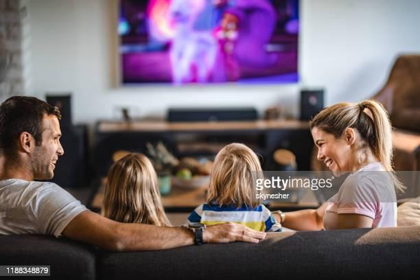 achteraanzicht van een familie tv kijken op de bank thuis. - televisie kijken stockfoto's en -beelden
