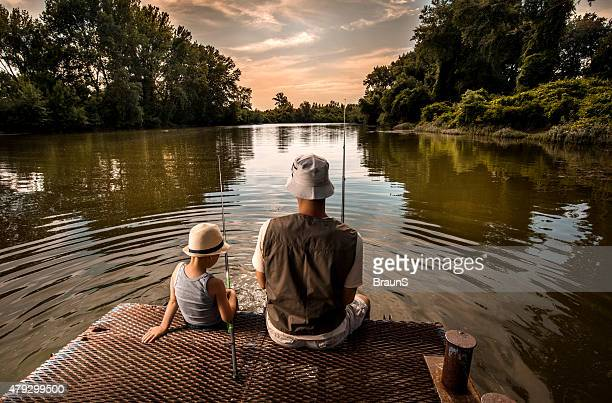 Rear view of a father and son fishing.