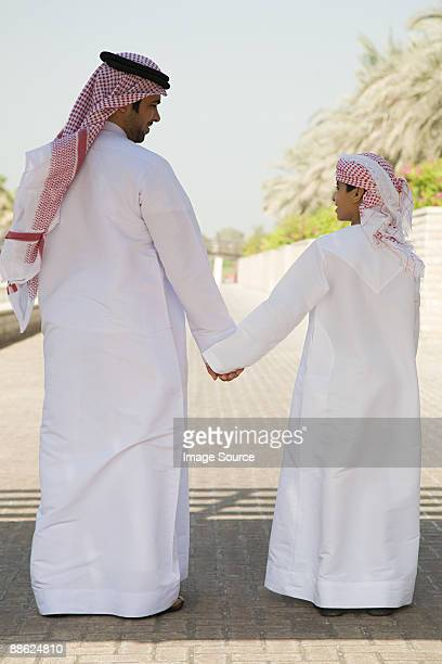 Rear view of a father and son holding hands