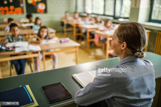 vista posteriore di un'insegnante elementare femminile che dà una lezione in classe. - maestra foto e immagini stock