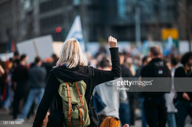 rear view of a female protester raising her fist up - social justice concept stock pictures, royalty-free photos & images