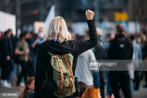rear view of a female protester raising her fist up - striker stock pictures, royalty-free photos & images