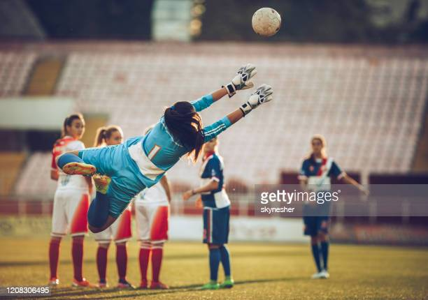 rear view of a female soccer goalie catching the ball after free kick on a match. - soccer competition stock pictures, royalty-free photos & images