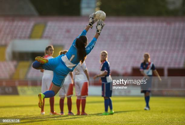 rear view of a female soccer goalie catching the ball after free kick on a match. - goalkeeper stock pictures, royalty-free photos & images