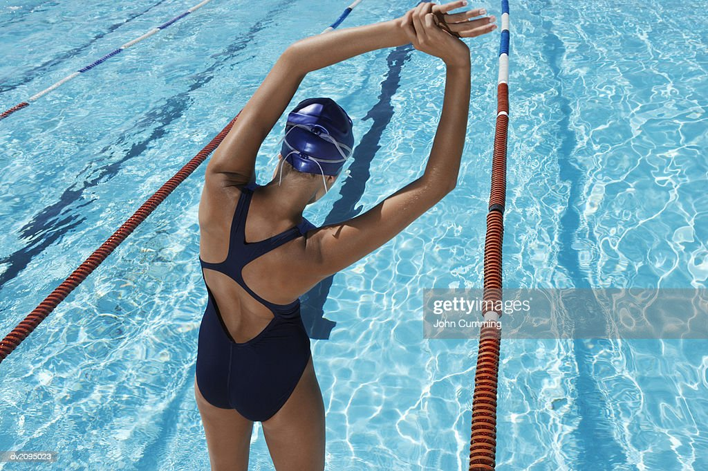 Rear View of a Female Swimmer Stretching in Front of a Swimming Pool : Stock Photo