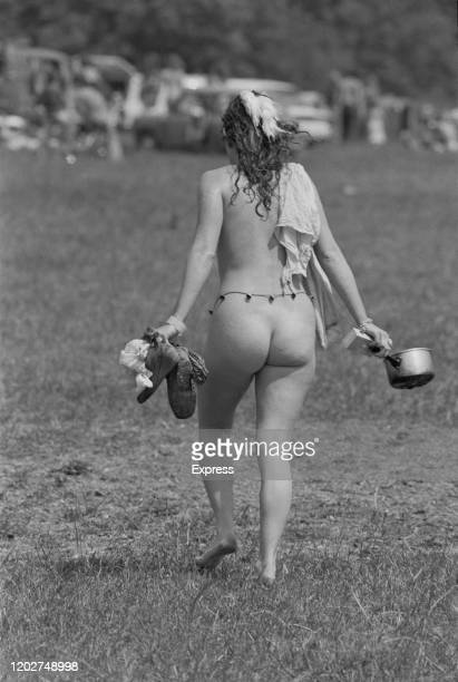 A rear view of a festival goer wearing only a cord around her waist upon on which tiny bells hang while carrying a pair of boots in one hand and a...