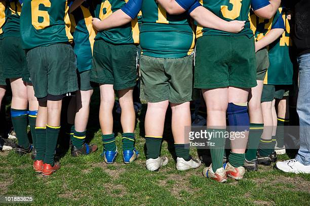 Rear view of a football team huddled together,  Melbourne, Victoria, Australia