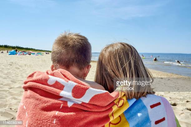 rear view of a girl and a boy covered in a towel and sitting together on a beach - brother stock pictures, royalty-free photos & images