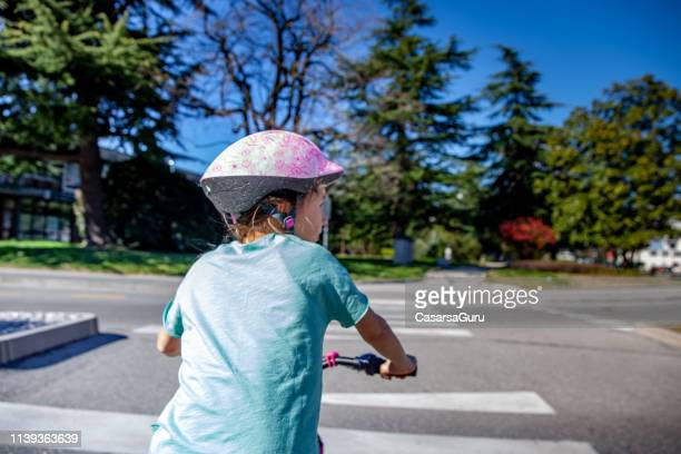 rear view of a girl crossing the street with her bicycle - waist up stock pictures, royalty-free photos & images