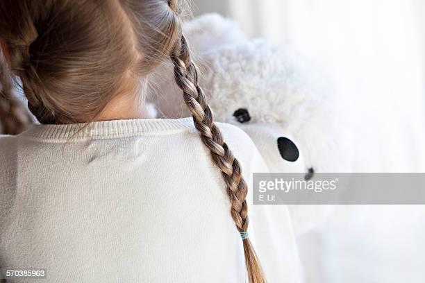 Rear view of a girl Hugging a teddy Bear