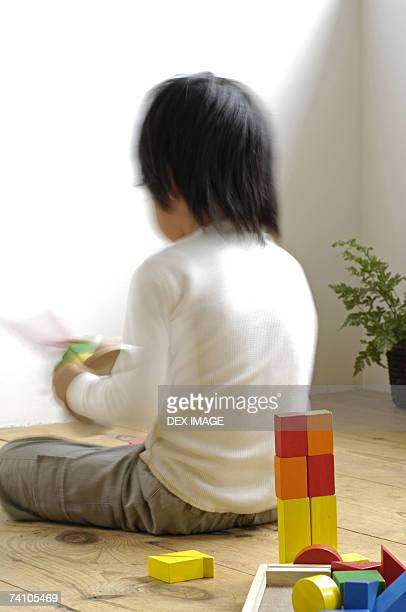 Rear view of a girl playing with toys