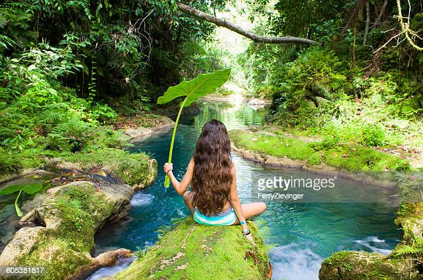 Rear view of a Girl sitting by the river holding a large leaf, Jamaica, Caribbean