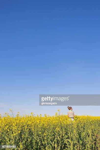 Rear view of a girl standing in canola field, Perth, Western Australia, Australia