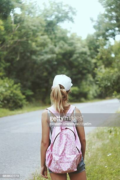 Rear View Of A Girl Standing On Country Road