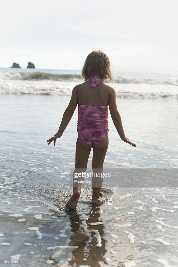Rear view of a girl standing on the beach : Foto de stock