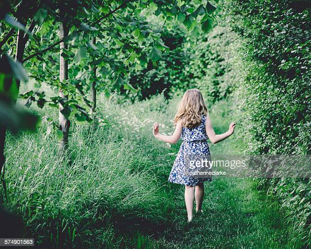 Rear view of a girl walking through forest