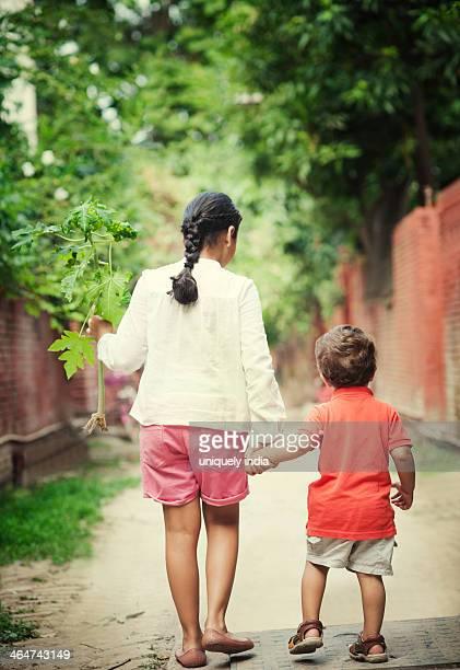 Rear view of a girl with her brother walking on the street