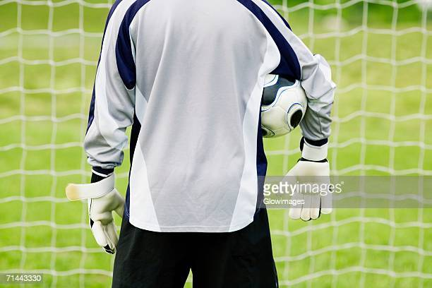 Rear view of a goalie with a soccer ball under his arm