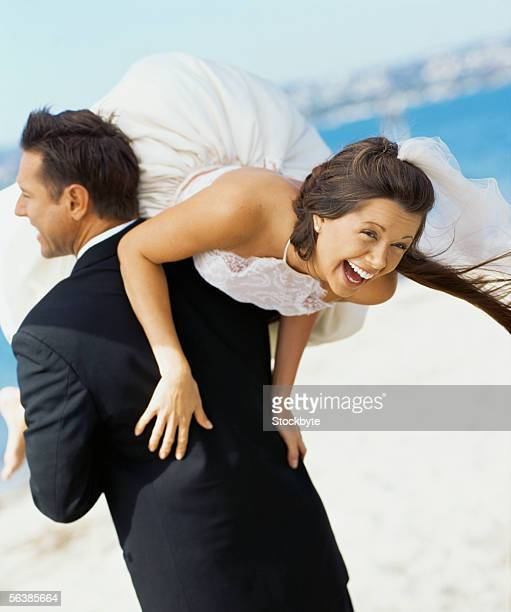 rear view of a groom carrying his bride on his shoulders