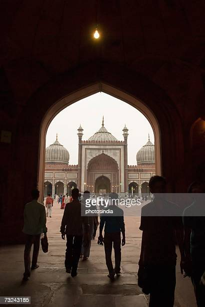 rear view of a group of people entering a mosque, jama masjid, new delhi, india - jama masjid delhi stock pictures, royalty-free photos & images