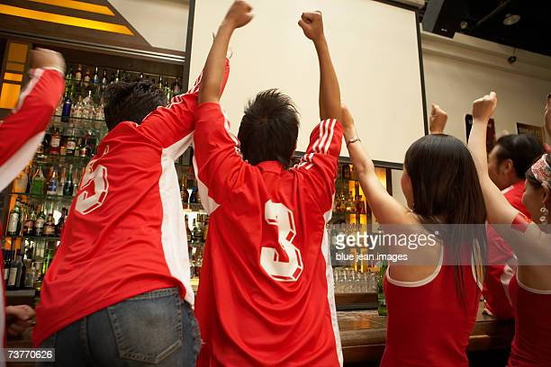 Rear view of a group of sports fans in matching clothing celebrating a victory at a sports bar