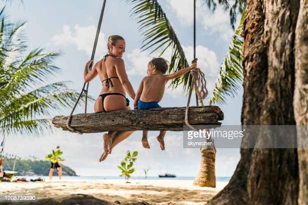 vista trasera de una feliz madre soltera e hijo balanceándose en la playa. - tanga fotografías e imágenes de stock