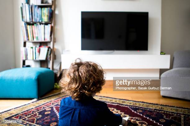 rear view of a kid sitting and watching television - living room stock pictures, royalty-free photos & images