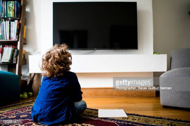 rear view of a kid sitting and watching television - watching stock pictures, royalty-free photos & images