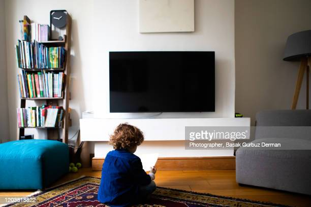 rear view of a kid sitting in front of tv and reading a book - domestic room stock pictures, royalty-free photos & images