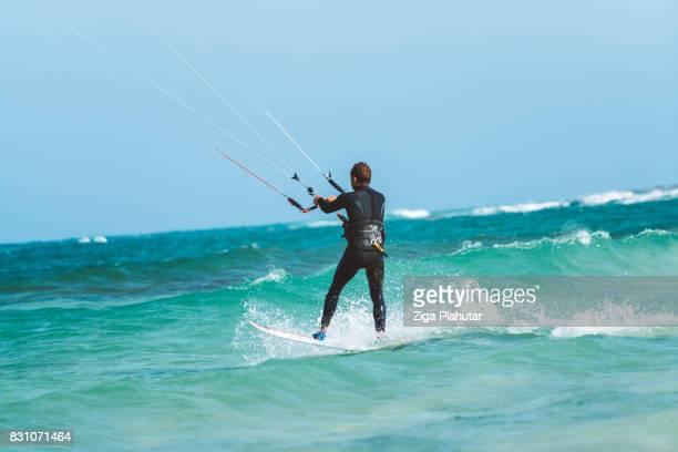 Rear view of a kiteboarder standing on kiteboard in blue water