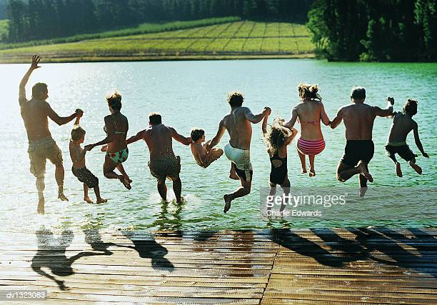 Rear View of a Large Family Group Jumping in a Lake Together