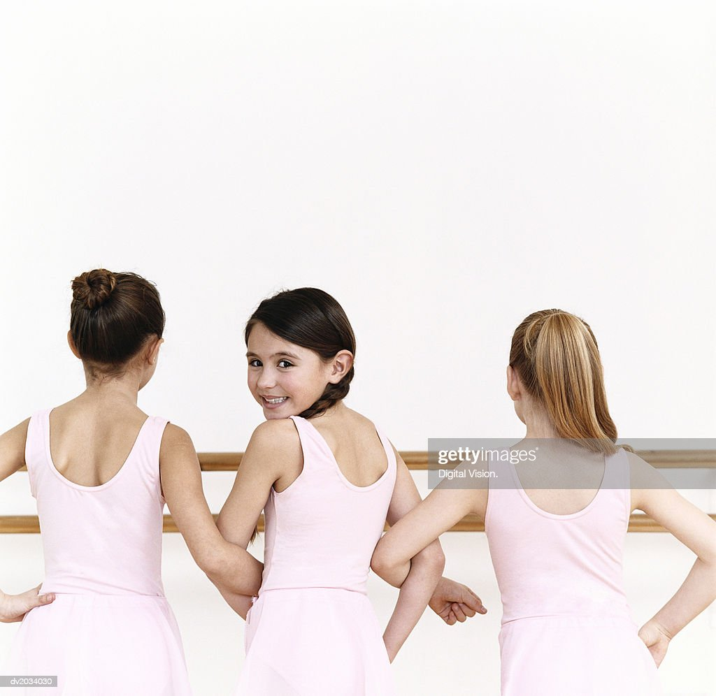 Rear View of a Line of Young, Female Ballet Dancer Practicing in the Dance Studio With One Ballerina Looking Behind Her : Stock Photo