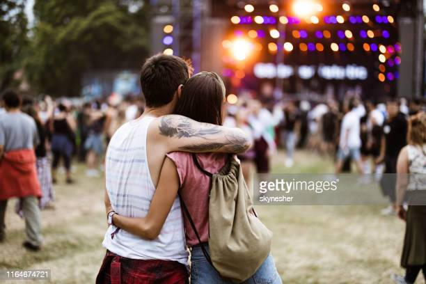 rear view of a loving couple embracing while enjoying in music concert. - close to stock pictures, royalty-free photos & images