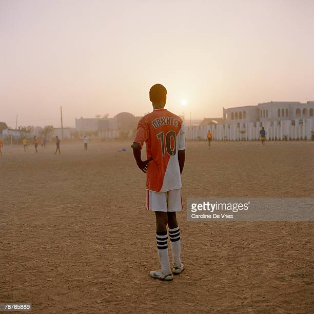 Rear view of a male standing on a sports ground