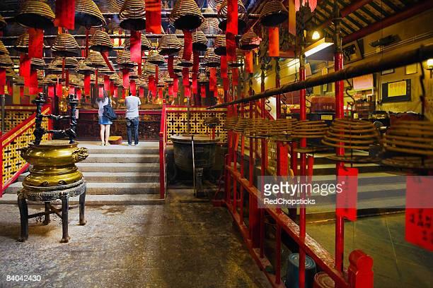 rear view of a man and a woman praying in a temple, man mo temple, hong kong, china - man motempel stockfoto's en -beelden