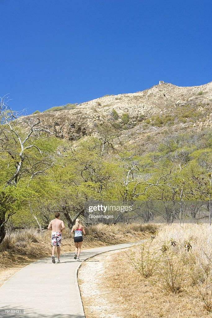 Rear view of a man and a woman running on a path, Diamond Head, Waikiki Beach, Honolulu, Oahu, Hawaii Islands, USA : Foto de stock