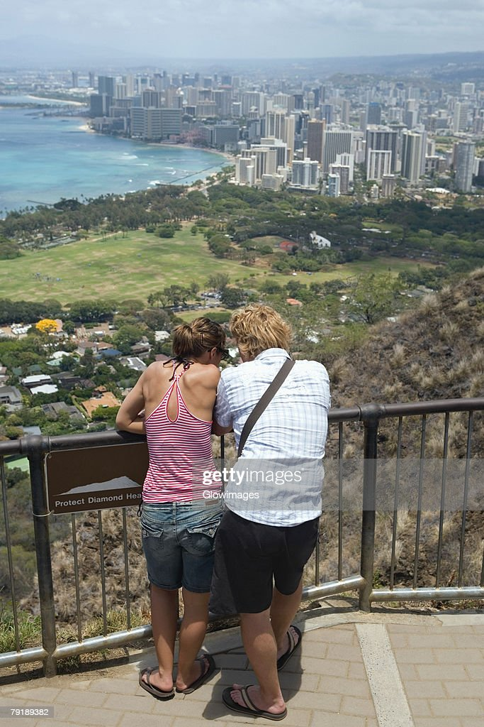 Rear view of a man and a woman standing at an observation point, Diamond Head, Waikiki Beach, Honolulu, Oahu, Hawaii Islands, USA : Stock Photo