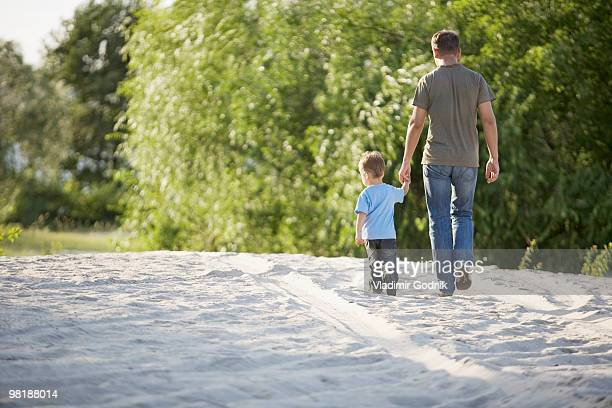 Rear view of a man and a young boy walking hand in hand